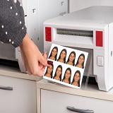 Just printed passport photos exiting a printer